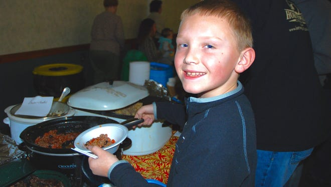 Peyton Witmer, of South Lebanon, helps himself to a bowl of elk chili at last month's Wild Foods Dinner in Pine Grove.