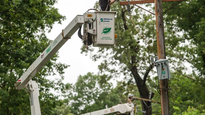 Delmarva Power crews work to repair damage poles on Welsh Tract Road in Newark following a storm July 1, 2013.