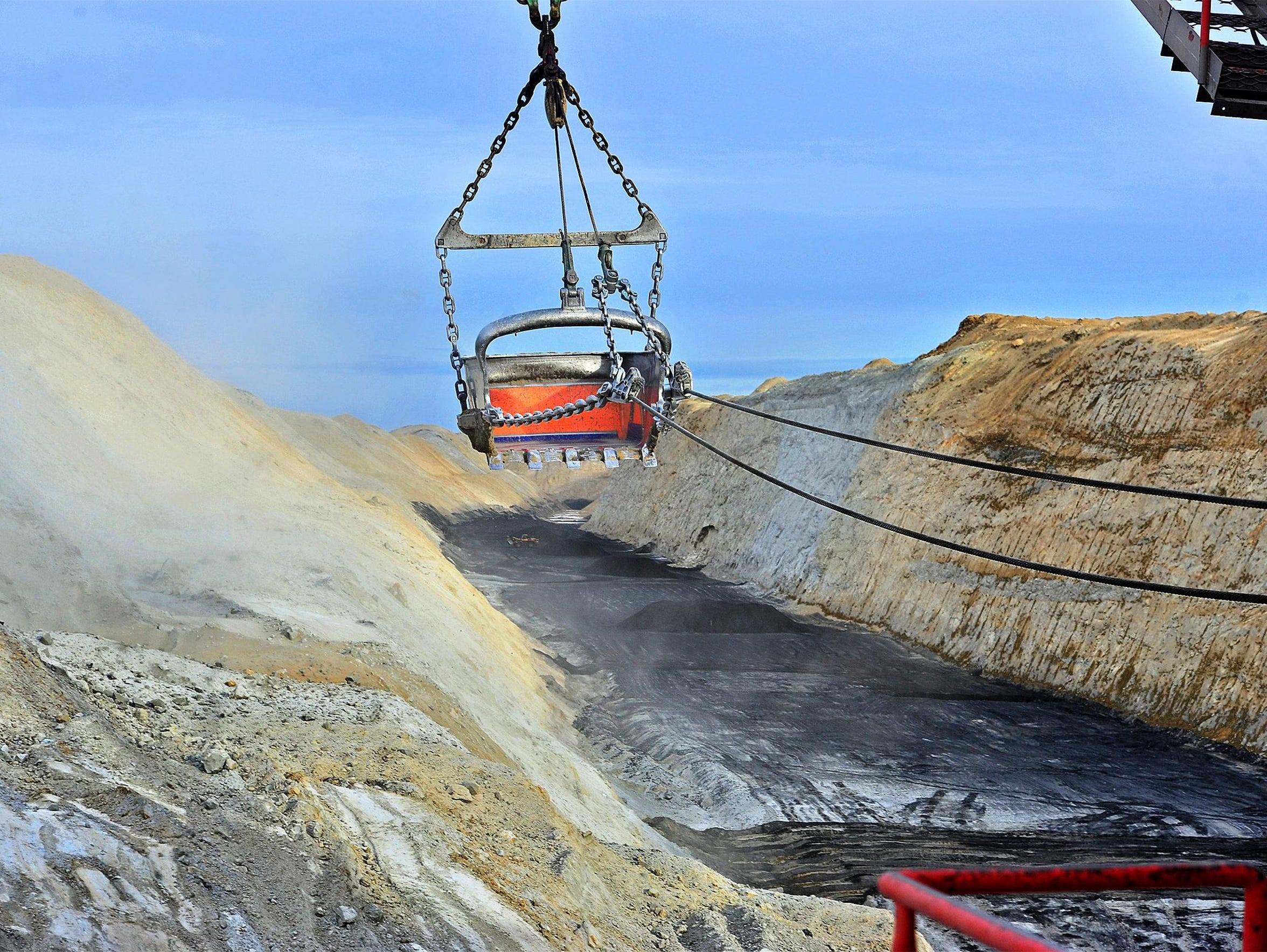 A dragline earth mover does the heavy lifting in uncovering