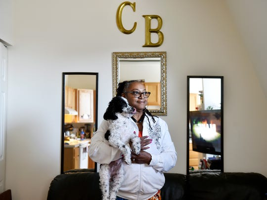 Connie Brown-Scott, 62, stands with her dog Bella in her West York apartment. Brown-Scott used to live where the York Revolution's stadium now stands. Her house was where the parking lot directly outside the ticket office is now.