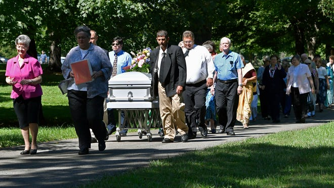 The casket containing the remains of Sister Paula Merrill, leads the processional into the cemetery following her funeral service, Friday, Sept. 2, 2016, at St. Vincent Church in Bardstown, Ky. Sister Merrill, with the Sisters of Charity of Nazareth and another nun were found murdered in their home on Aug. 25 in Durant, Miss.