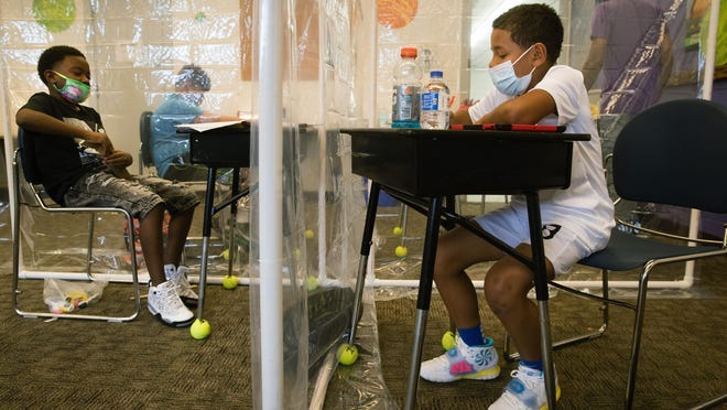Separated by walls of hanging plastic to mitigate the threat of COVID-19, fifth grade students DJ Coleman, left, and Ashton Kirkwood tends to his schoolwork at the Boys and Girls Clubs of Central Illinois during the first day of the new school year for Springfield School District 186 Monday, Aug. 31, 2020.