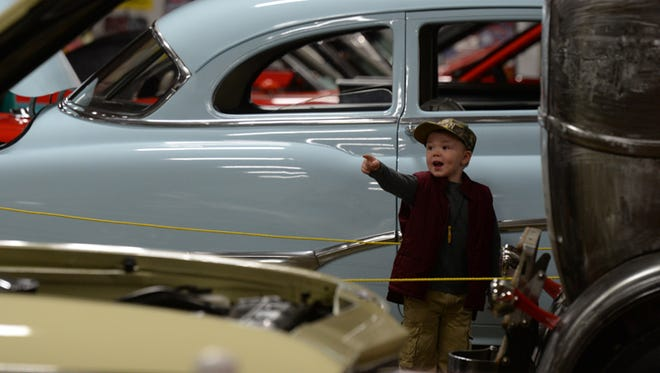 Coltin Taylor points to a car inside the Tom Raper Center for the annual Vintage Wheels show.