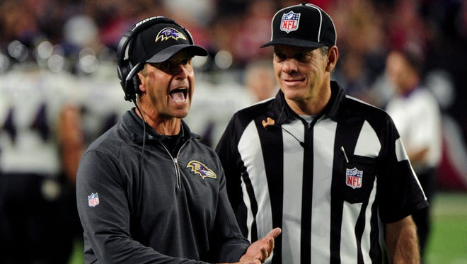 Baltimore Ravens head coach John Harbaugh talks with side judge Scott Edwards (3) during the first half against the Cardinals at University of Phoenix Stadium.