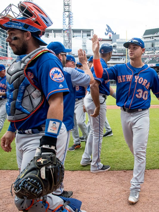 New York Mets left fielder Michael Conforto (30) and catcher Rene Rivera, left, come off the field after a baseball game against the Atlanta Braves, Sunday, June 11, 2017, in Atlanta. New York won 2-1. (AP Photo/John Amis)
