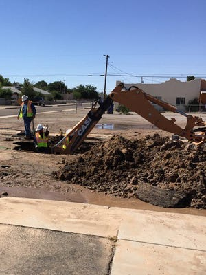 City of Las Cruces employees work to fix a broken water main at Fourth and Brownlee Thursday, June 16, 2016.