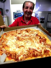Erminio Iantosca, owner of Mama Mia's, proudly shows off his handcrafted pizza at his Naples location.