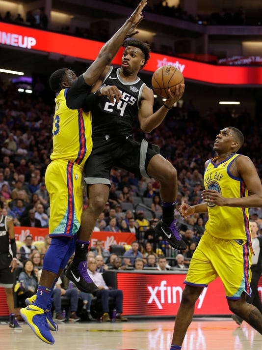 FILE - In this March 31, 2018, file photo, Sacramento Kings guard Buddy Hield, center, goes to the basket against Golden State Warriors forward Draymond Green, left, during the second half of an NBA basketball game in Sacramento, Calif. For the 12th straight season the Kings have failed to make the playoffs, extending the longest active playoff drought in the NBA but, there is some reason for optimism. Hield, who is completing his second year in the NBA, is among several key players age 25 or younger for the franchise that is trying to build a winning team. (AP Photo/Rich Pedroncelli, File)