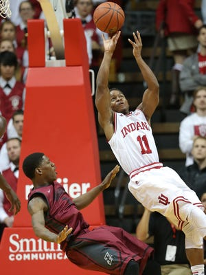 Indiana Hoosiers guard Yogi Ferrell glides under the basket after being fouled by Greyhound Dai-Jon Parker in the first half. Indiana hosted the University of Indianapolis in a preseason game at Assembly Hall on Monday, November 10, 2014.