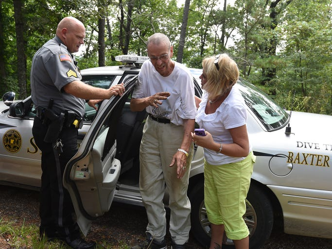 Sgt. Mike Holland (from left) helps George Salo from his squad car while Mary Cooper, of Home Bound Medical, assists. Salo was reported missing Monday morning from his Norfork home and was found several hours later more than a mile away by the White River.