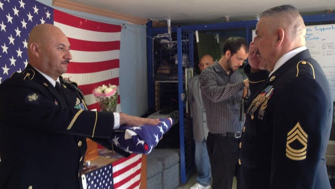 Hector Barajas, 39, folds an American flag to be placed with the remains of a deported veteran who died in Mexico. The remains were allowed to be returned to the U.S. for burial. The flag presentation before Cesar Medrano (right) took Spc. Chaides' remains back to U.S. soil.