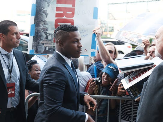 Actor John Boyega signs autographs while arriving for