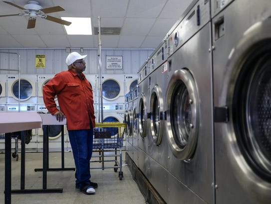 """Roy Swanson of Detroit watches his clothes wash at Super Clean Coin Laundry on E. 7 Mile in Detroit on Thursday April 19, 2018. """"It feels a little safer. I think that the bad guys know that the cameras are on here as well,"""" Swanson said about the comfort of the business being a part of the Green Light Program with the Detroit Police Department."""