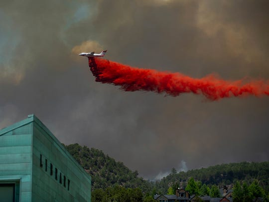 A plane drops fire retardant on homes in the area of