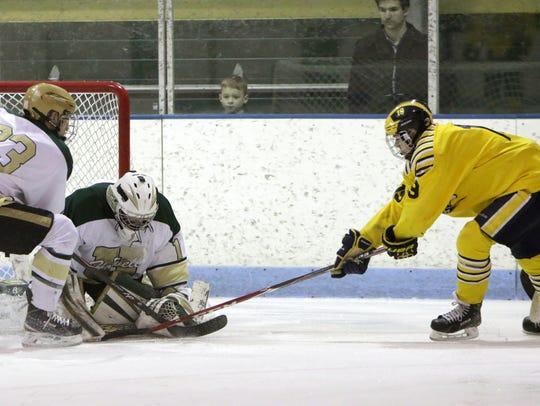 Howell goalie Nathan George denies Hartland's Blake