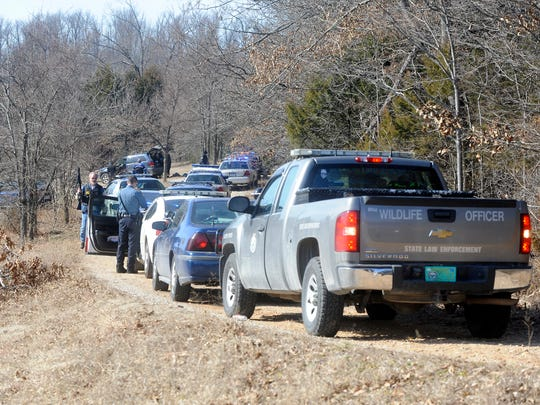 Area law enforcement vehicles line a driveway to a house where Jerry Dean Hopper Jr., 41, held officers at bay for more than an hour on Thursday.