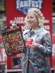 "Tricia Suit of Northside holds up her prize after using her phone to tweet at the All-Star Game ""Twitter vending machine"" for prizes on Fountain Square at FanFest on March 9."