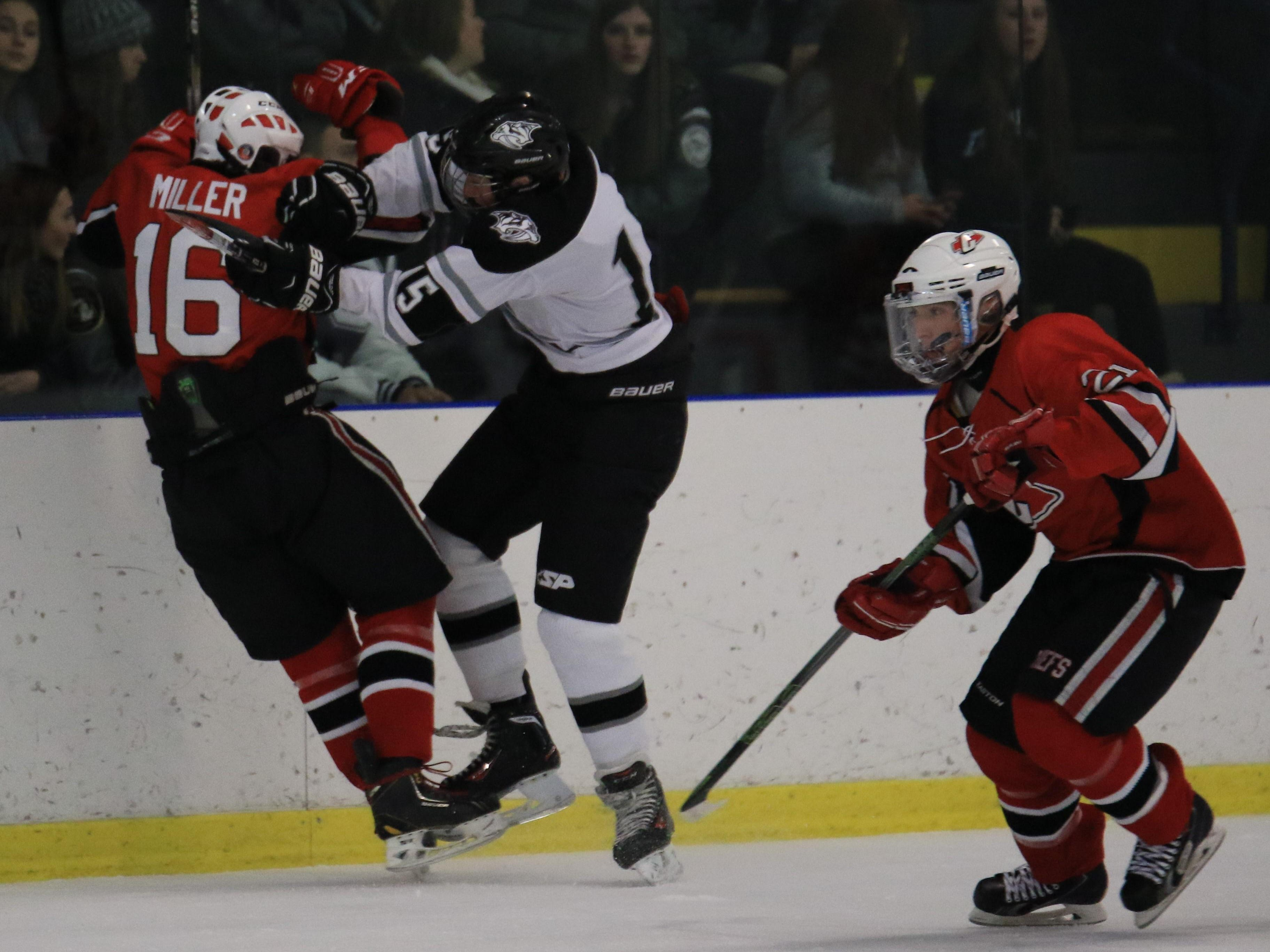 Delivering a hard body check against Canton's Jalen Miller (No. 16) is Plymouth's Christian Mullenax.