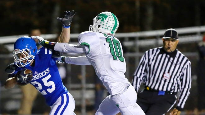 Catholic Central's Nicholas Capatina (left) eludes the grasp of Novi tackler Ryan Welch in Friday's district final.