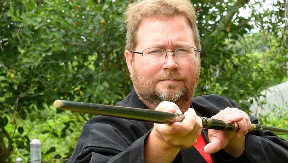 Mike Tripp with martial arts bo staff.