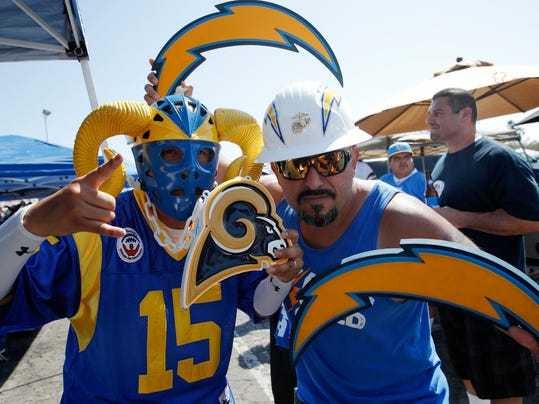 Los Angeles Rams fan Paul Castaneda, left, and Los Angeles Chargers fan Bryan Bahr pose before a preseason NFL football game Saturday, Aug. 26, 2017, in Los Angeles. (AP Photo/Jae C. Hong)