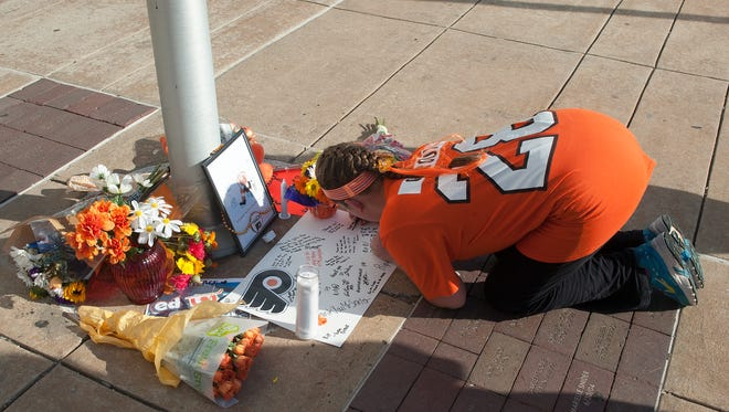 Flyers fan Gigi Fiordimondo, writes a message on a small memorial along the entrance of the Wells Fargo Center in memory of Ed Snider.