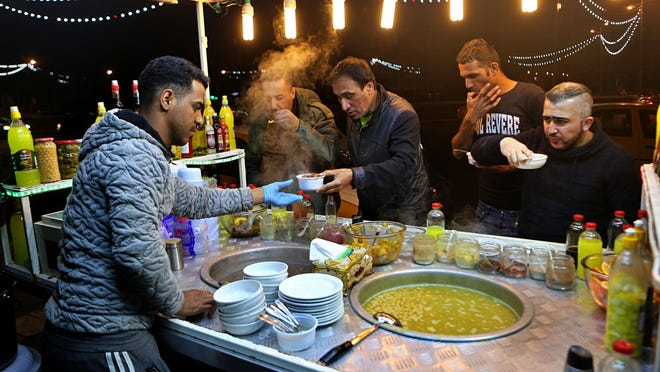 In this Feb. 13, 2019 photo, a chickpeas vendor serves customers in Tahrir Square in Baghdad, Iraq. For the first time in 15 years, Iraq is not at war. The defeat of the Islamic State group after a ruinous four-year war has given the population a moment of respite, and across the capital Baghdad there is a guarded sense of hope.