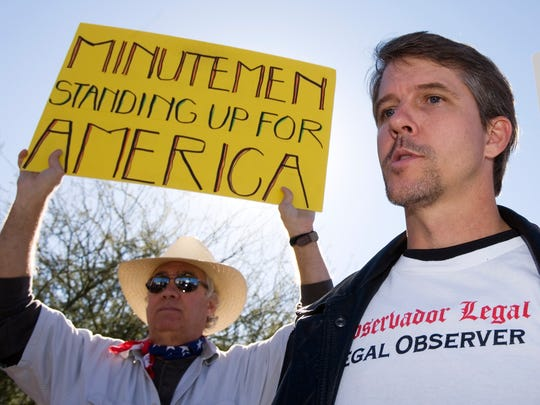 Chris Simcox, founder of the Minuteman Project, is flanked by members of the group at a Minuteman picket of a street corner in Phoenix in 2005.
