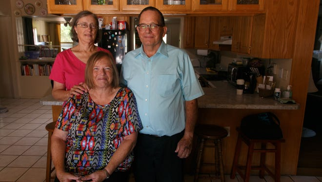 Marie Vaughan, her sister, Jan Owen and Owen's husband, Ken, from left, lose for a portrait in the St. George home into which Logan Aitken and his company, Kind Hearts Senior Care, helped them move.
