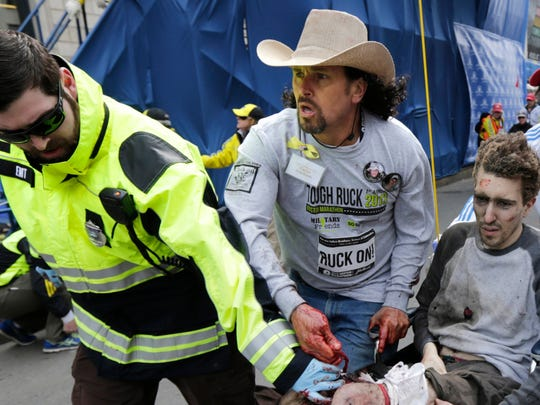 Boston EMT Paul Mitchell, left, and bystander Carlos Arredondo (in cowboy hat) push Jeff Bauman in a wheelchair after he was injured in one of two explosions near the finish line of the Boston Marathon. Bauman and his three rescuers became one of the most powerful symbols of Boston's resilience after the April 15, 2013, attacks.