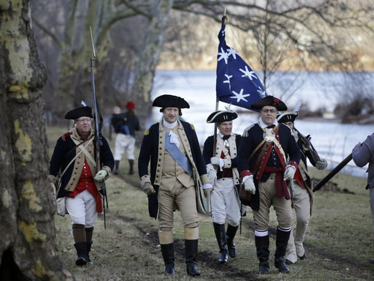 George Washington, played by John Godzieba, second from left, walks with troops in Washington Crossing, Pa., near the Delaware River during a re-enactment of Washington's daring Christmas 1776 crossing of the Delaware River