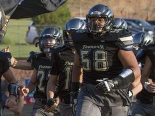 Penei Sewell (No. 58)  runs out on the field before a Desert Hills football game.