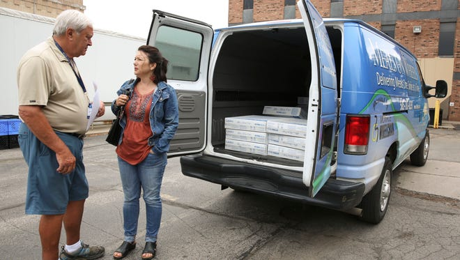 Charles Frank, a Meals on Wheels Driver and Server, talks with Fan Club founder Maria Friske outside the Meals on Wheels delivery truck before the two head out to deliver fans to low-income seniors in their homes.