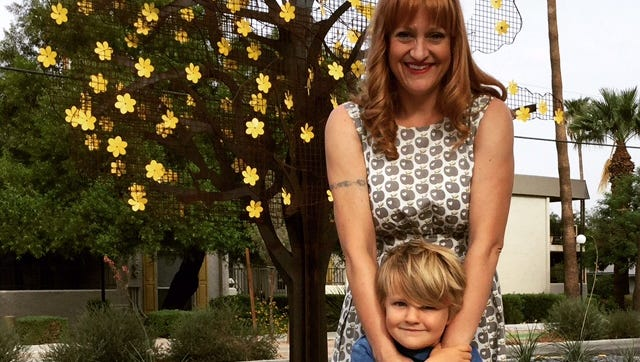 """Tempe artist Melissa Martinez and her son Theo stand in front of her public-art installation """"In Bloom"""" on Hardy Drive just south of 13th Street."""
