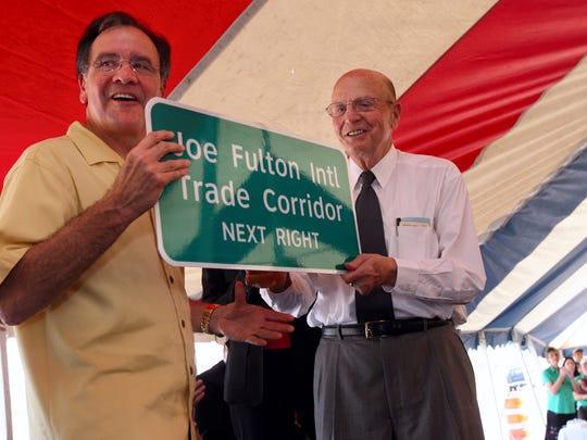 Port of Corpus Christi Chairman Ruben Bonilla (cq,left) presents Joe Fulton (cq,right) with a highway roadsign during the ceremonies celebrating the opening of the Joe Fulton International Trade Corridor Thursday.
