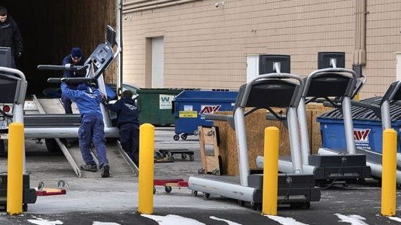 Workers remove equipment from the former Work Out World Fitness gym on Dec. 29.