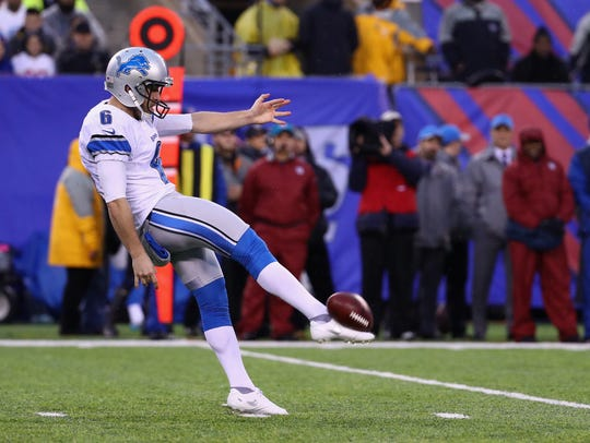 Lions punter Sam Martin punts the ball against the