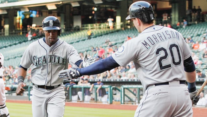 Seattle Mariners' Austin Jackson, left, receives congratulations from Logan Morrison, right, after scoring against the Houston Astros in the first inning in a baseball game Thursday April 30, 2015 in Houston.