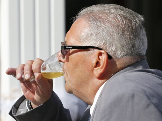 Tommy DiPaolo drinks sparkling cider after giving the toast at his son's wedding ceremony.