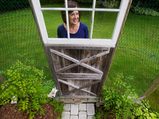 Kate Pelkey shows off a unique trellis that, once it fills in, will resemble a garden door.