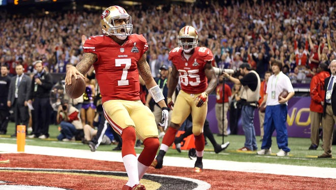 San Francisco 49ers quarterback Colin Kaepernick (7) scores a touchdown against the Baltimore Ravens in the fourth quarter in Super Bowl XLVII at the Mercedes-Benz Superdome.