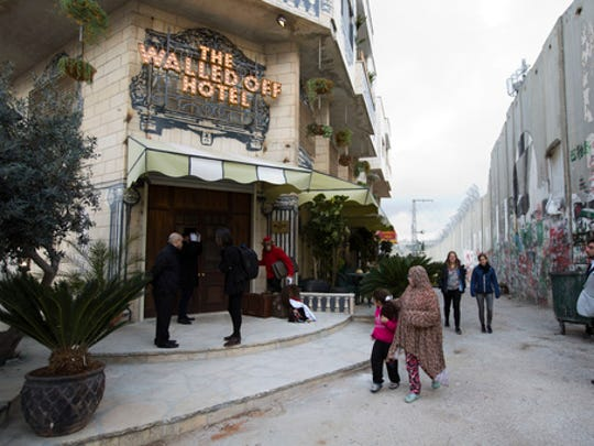 "People pass by the ""The Walled Off Hotel"" and the Israeli"