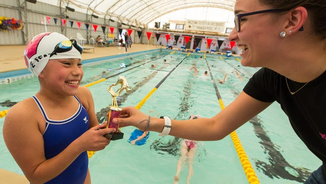Wild West Aquatic Club assistant coach Kelsey Andersen, right, gives Zoey Herrera, 9, a trophy from the team  on Tuesday, April 5, 2016, for her state record-breaking time in the 200 individual medley that she set at a meet last September. Herrera's time was 3:05.48 and set the record for girls 8 years old and under in New Mexico.