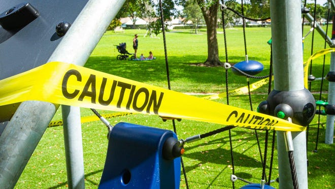 Caution tape wraps the playground equipment at a Boynton Beach park, Wednesday, April 29, 2020. A mom and her two children came to the park, expecting it to be open.