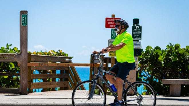 A man with a face mask bicycles north past Beach Access 51 on Ocean Blvd in Jupiter, Monday, May 4, 2020.