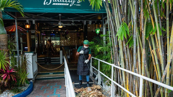 An employee of E.R. Bradley's in West Palm Beach sweeps up before the reopening May 11. .
