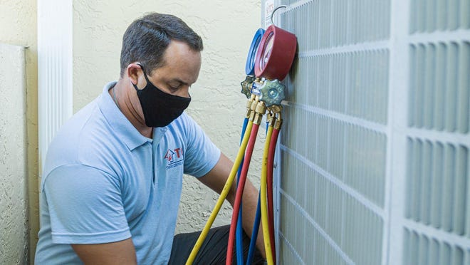 Rey Rivera, co-owner of TCS (Temperature Control Solutions) in West Palm Beach, works on an air conditioner compressor in Lake Worth on Wednesday, July 1, 2020.