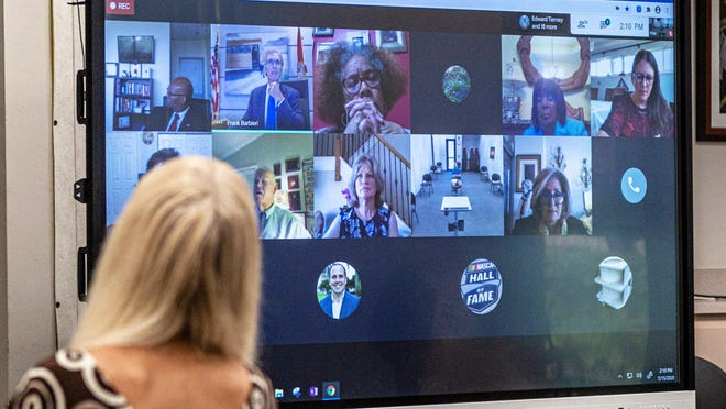 Retired teacher Linda Gonzalez watches a virtual meeting of the Palm Beach County School Board meeting Wednesday from the school district's headquarters in Palm Springs. Residents were invited to comment on the school district's proposed reopening plan in person.