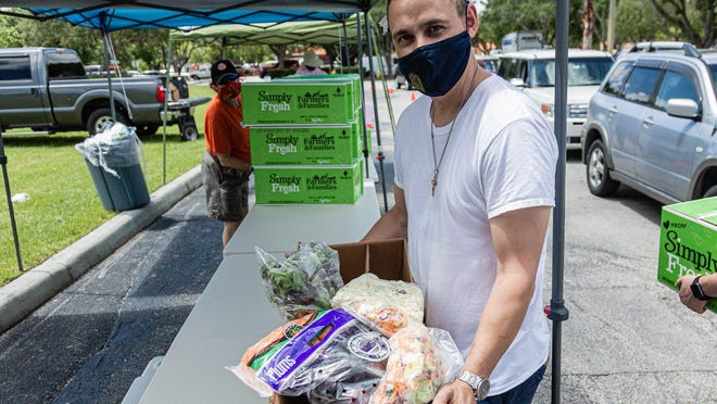Joseph Water, the First Vice President of the West Palm Beach Chapter of the American Culinary Federation, holds one of the boxes of produce being distributed for free in the parking lot of the Home Depot on Northlake Blvd. in Lake Park, Friday, July 24, 2020. In conjunction with Home Depot, the ACF has been distributing food at this location for the past three Fridays and will back for the next three Fridays. Over 1,440 boxes of produce will be distributed today. The boxes contain various items of fresh produce including lettuce, plums and other fruits and vegetables.