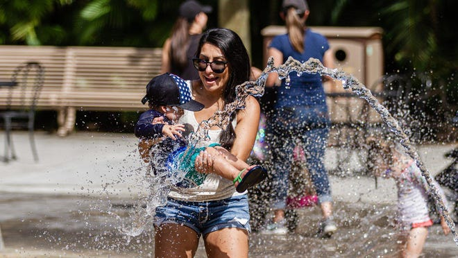A mother plays with her son in the Fountain Plaza splash pad at Dreher Park Zoo in West Palm Beach, Tuesday, June 30, 2020. The zoo is operating at reduced capacity, and there is a one-way path designated throughout the zoo.